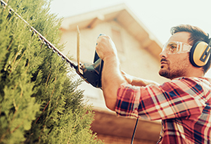 Man wearing hearing protection while trimming trees