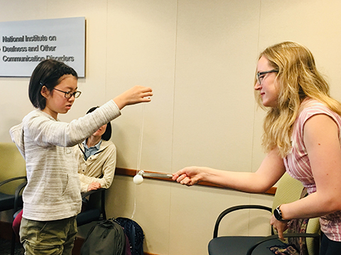 A woman holding a tuning fork next to a ping pong ball attached to a string that a girl is holding.