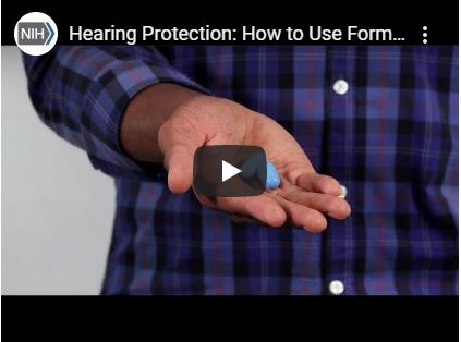 A screenshot of video depicting an adult hand holding formable earplugs.