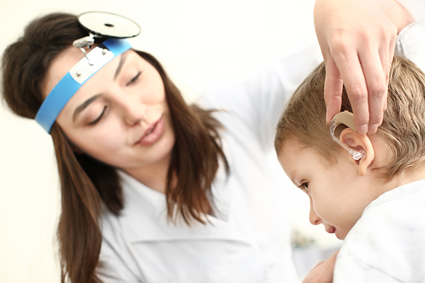 A doctor helping to place a hearing aid on a child.