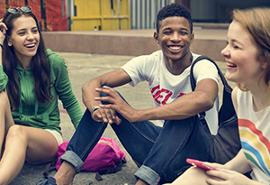 Three teenagers sitting on the ground laughing and talking with each other.
