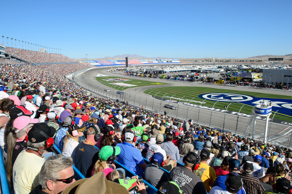 Fans sitting in the stands at a racecar event.