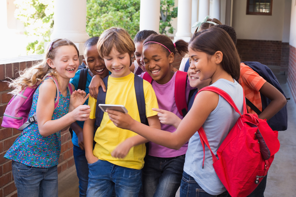 A group of children standing in the hallway of a school looking at a mobile device.