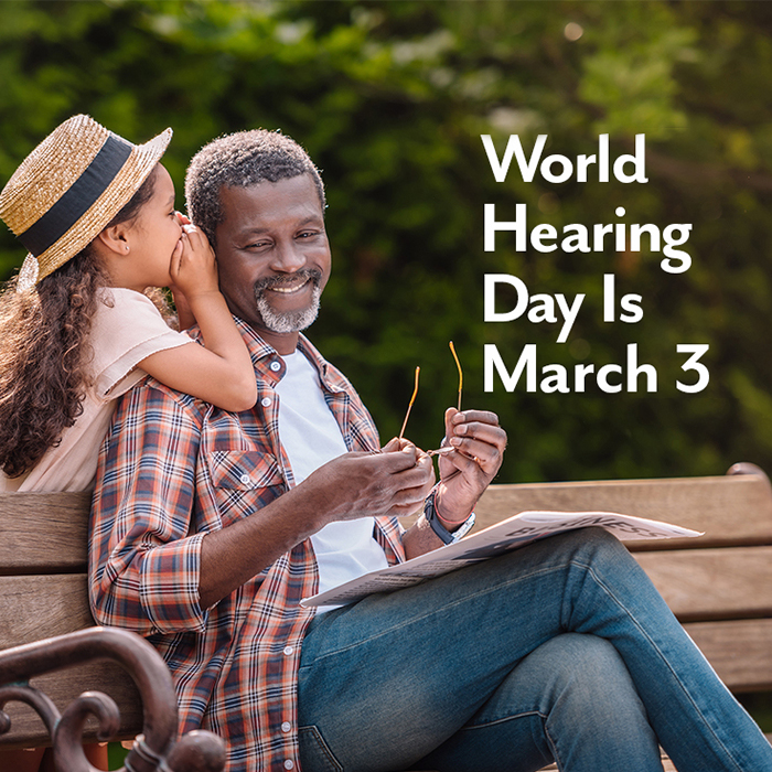 Young girl whispering to her grandfather who is sitting on a park bench. Text: World Hearing Day Is March 3