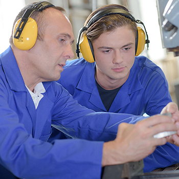 Two workers doing work while wearing ear protection