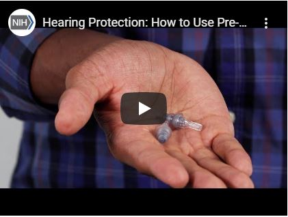 A screenshot of video depicting an adult hand holding pre-molded earplugs.