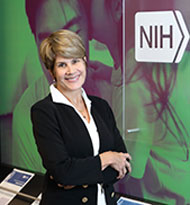 An image of Dr. Tucci standing in a hallway next to a sign that reads, 'NIH National Institute on Deafness and Other Communication Disorders.'