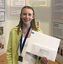 13-year-old Nora Keegan stands in front of a poster presentation detailing her research.