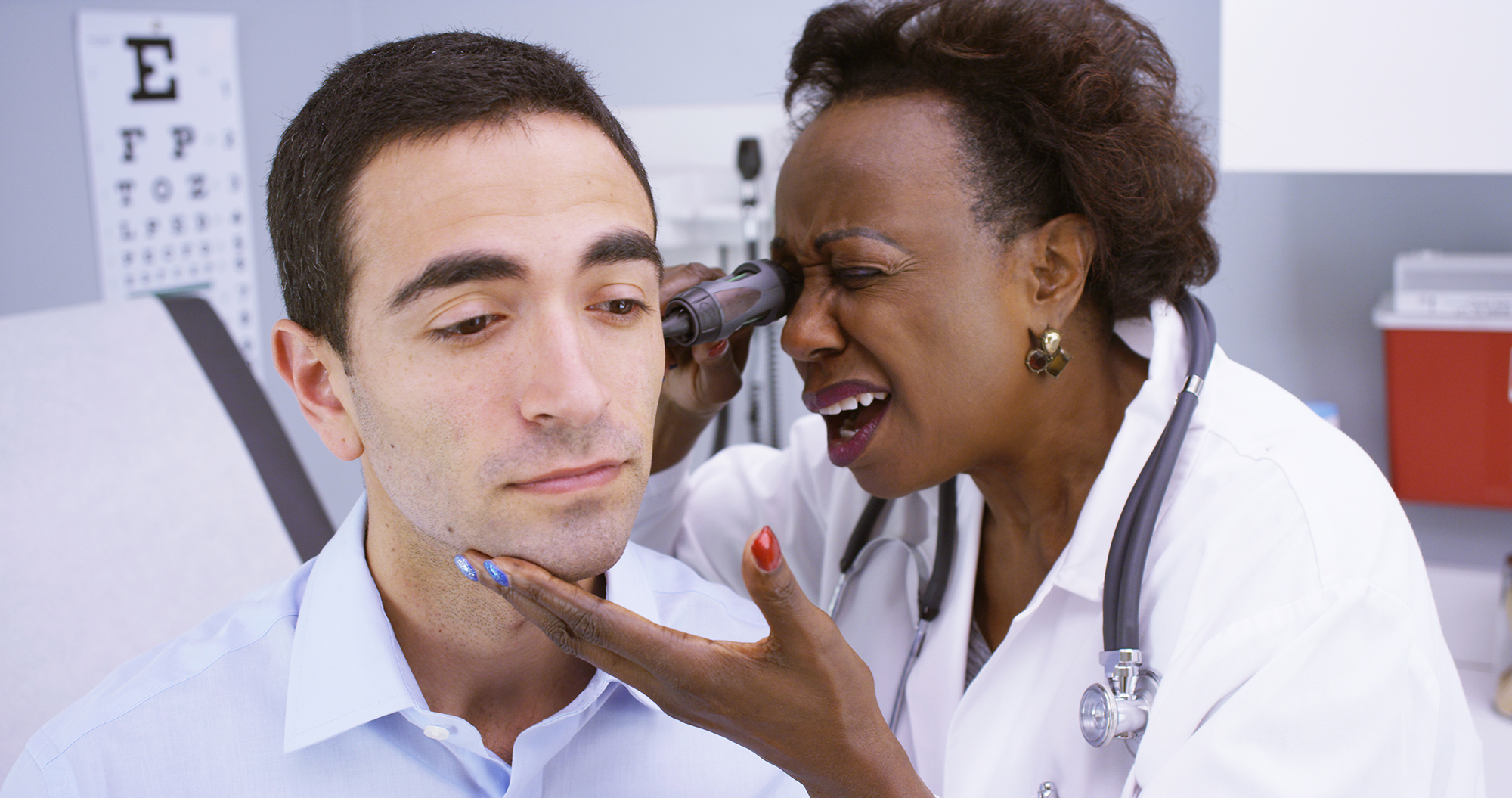 Doctor inspecting patient's ear