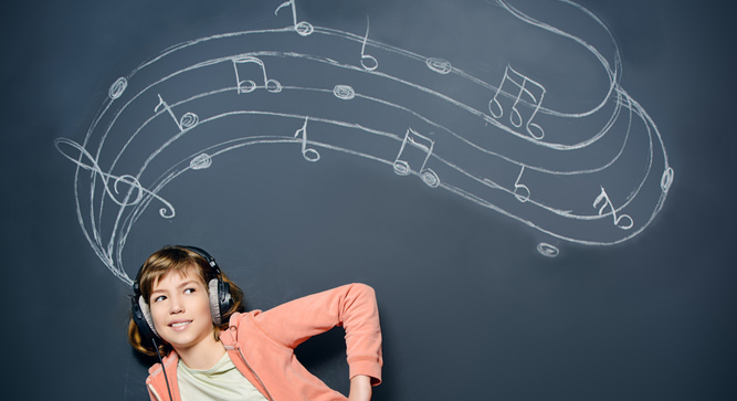 Young girl wearing a personal music device. She is standing in front of a blackboard that has musical notes written in chalk.