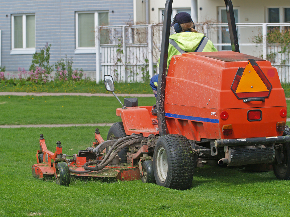 A large mowing tractor being driven across a lawn by an adult male.