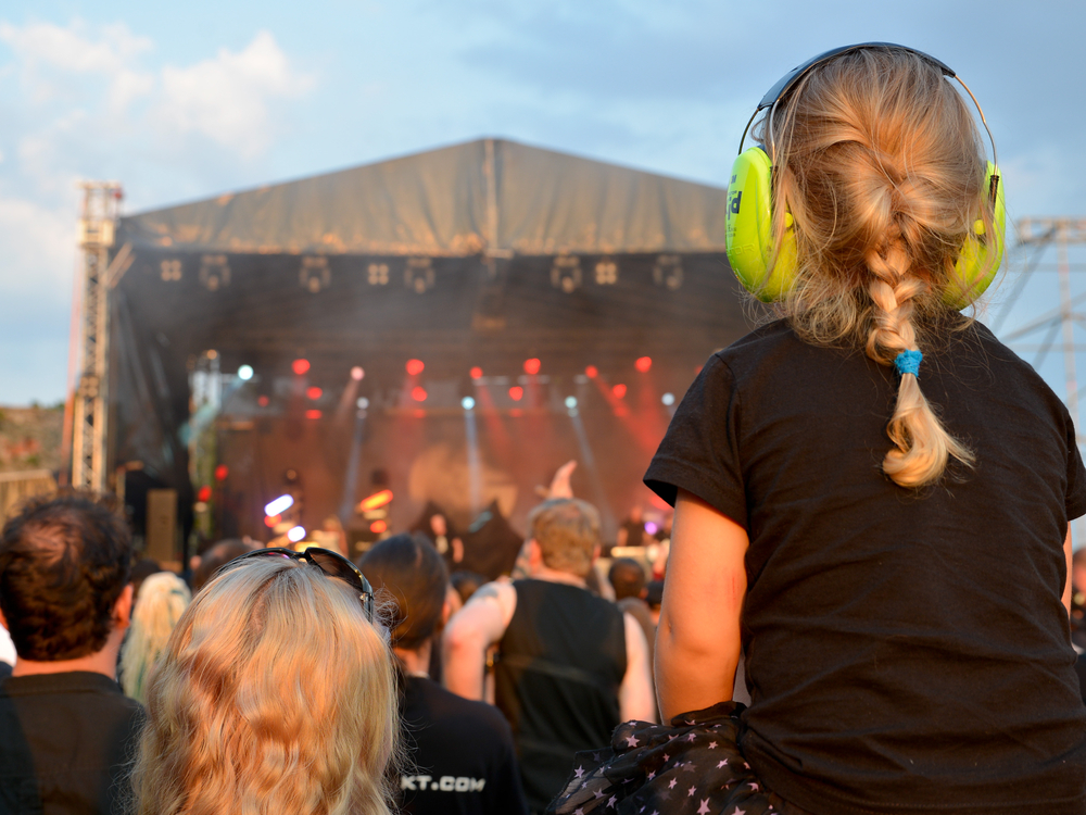 Child with ear muffs on at concert