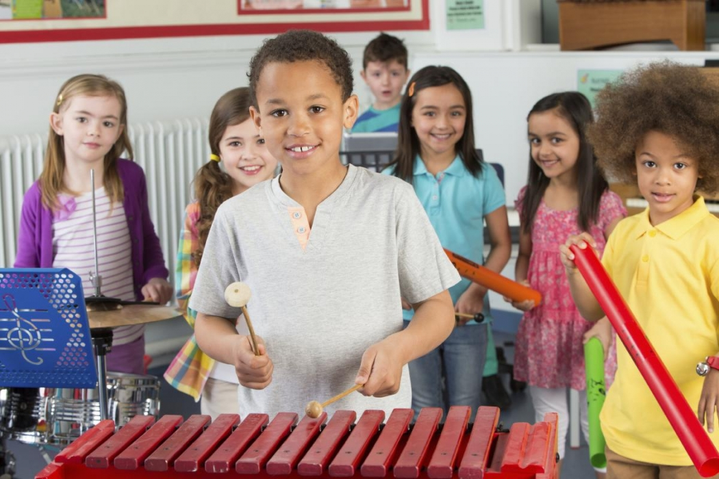 Chlidren playing musical instruments and smiling.
