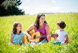 A mother teaches her children to play guitar in a field on a sunny day