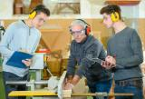 Male students wearing protective earphones in a woodwork class