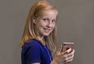 A preteen girl holds a smartphone in her hand and listens to music through earbuds.