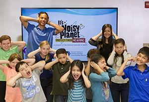 Two educators and about a dozen students, approximately ages 8 to 12, hold their hands over the ears as if the room is very loud. A slide from the Noisy Planet Teacher Toolkit is visible on a large screen behind the group.