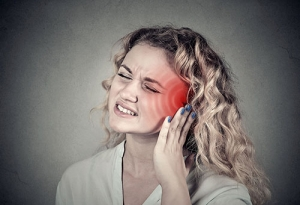 A young woman holds her ear while grimacing in pain.