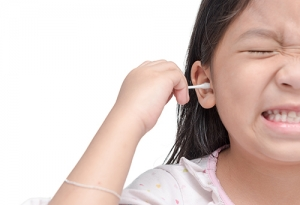 A young girl wincing as she cleans her ear with a cotton swab.
