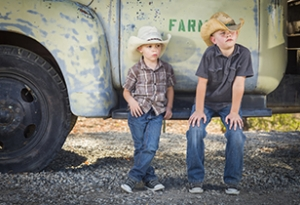 Two young boys wearing cowboy hats lean against an antique truck in a rustic country setting.
