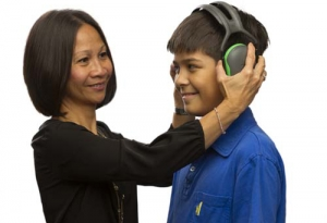 A women putting ear protection on a boy