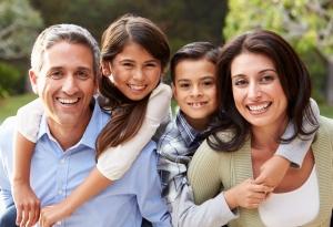 Un padre, una madre, hijo e hija sonriendo.