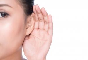 Una mujer joven con una mano sobre su oído intentando escuchar.