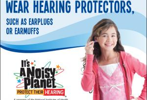 A young girl putting earplugs in her ears.
