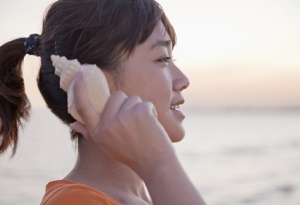 A woman holding a seashell next to her ear to hear the sound