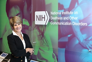"An image of Dr. Tucci standing in a hallway next to a sign that reads, ""NIH National Institute on Deafness and Other Communication Disorders"""