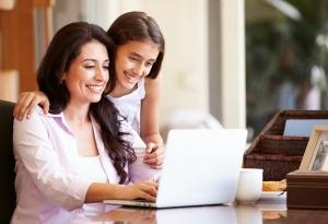 Una mujer y una niña mirando la pantalla de una computadora portátil.
