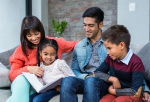 Una familia sentada en el sofá leyendo un libro.