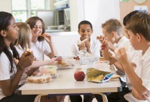 Niños en un colegio sentados alrededor de la mesa hablando y comiendo su almuerzo.