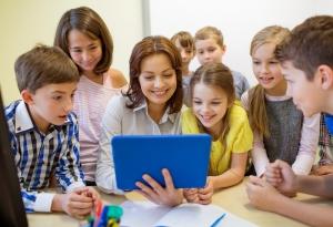 Una maestra y un grupo de niños están sentados en un salón de clase mirando una computadora tipo tableta.