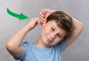 Screenshot of a GIF depicting young boy inserting a foam earplug.
