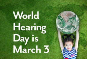 A young girl relaxes outdoors on the grass while holding a large ball that resembles the earth. The image reads: World Hearing Day is March 3.