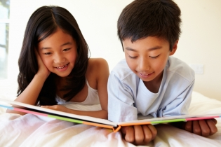 Children sitting on bed reading a book