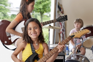 Young children in a garage playing guitars and drums.
