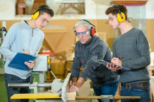 High school students and a teacher, who is using a power tool, wearing protective earphones in a woodworking class.