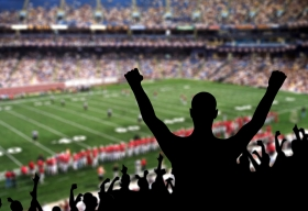 A fan cheering in the stands during a football game