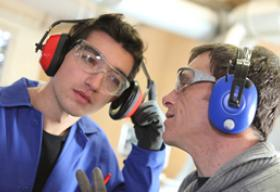 two factory workers wearing hearing protection