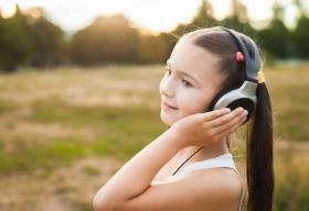 Una niña está al aire libre escuchando música con orejeras
