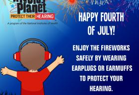 A young boy wears earmuffs to protect his hearing during a fireworks display.