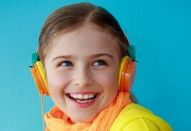 Girl in yellow with headphones on.