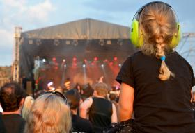 Child with protection earphones during concert