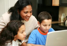 Woman and children looking at a computer screen together