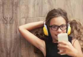Tween listening to device with earphones on.